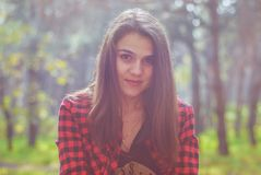 portrait of a beautiful girl wearing a plaid shirt on the background of the autumn forest royalty free stock photos