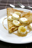 Warm banana pancake. Slices of banana served with maple syrup on warm pancake with melted butter Stock Photo