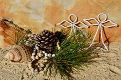 Warm Beach Christmas pine cone white beaded angels beach sand and shell Christmas in July. Warm Beach Christmas decoration pine cone with white beaded angels in Stock Images