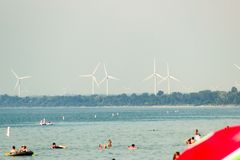 A warm beach with wind turbines in the back. Landscape view of beach with wind turbines in the background stock image