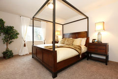 Warm beautiful bedroom with a high posts bed Royalty Free Stock Photos