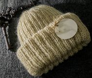Warm handmade beige winter hat for women with an emty tag on it. Warm and beautiful handmade beige winter hat for women with an emty tag on it Stock Photography