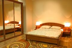 Warm bedroom. In orange and red. Classical bed and night lamps. Amazing colorful spiral carpet royalty free stock images