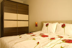 Warm bedroom. With wardrobe and large bed with pillows and roses sheets royalty free stock photography