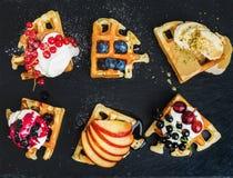 Warm belgian homemade waffles with fresh garden berries, fruit and ice cream on dark slate stone background Stock Image