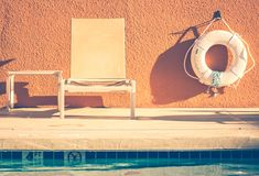 Summer bench and rescue tube by swimming pool stock image
