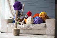 Warm binnenland met merinoswolballen in veelkleurig op witte sof Stock Afbeeldingen
