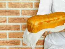 Warm bread in the baker`s hands. Warm and fresh bread in the baker`s hands. Baker is standing in front of the red brick wall royalty free stock photo