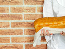 Warm bread in the baker`s hands. Warm and fresh bread in the baker`s hands. Baker is standing in front of the red brick wall stock images