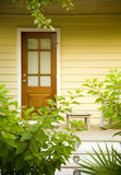 Warm brown door with plants and yellow wall. An inviting front yellow porch with wooden stairs and green plants in a garden Stock Photos