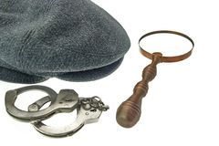 Warm Cap with Earflaps, Magnifying Glass and Handcuffs Stock Photo
