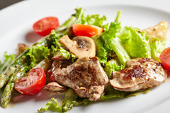 Warm Chicken Liver Salad. Restaurant and Gourmet Food - Warm Chicken Liver Salad with Mushrooms, Asparagus and Cherry Tomato Royalty Free Stock Photo