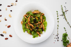 Warm chicken salad on kitchen table flat lay. Top view on cooking workplace with ingredients and side dish with vegetable and poultry meat. Recipe, healthy Royalty Free Stock Images