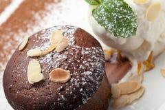 Warm chocolate cake Fondant with ice-cream ball, almond, mint, c. Warm dessert chocolate cake Fondant served on plate with ice-cream ball, almond chips, mint stock image