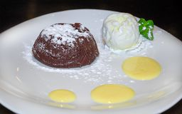 Warm chocolate fondant with a scoop of ice cream and strawberrie. S on a white plate stock photography