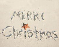 Warm Christmas greeting. Merry christmas greeting in the sand with starfish Royalty Free Stock Image
