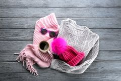 Warm clothes with cup of coffee and sunglasses. On wooden background. Winter vacation concept royalty free stock images