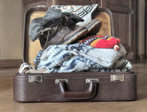 Warm cloths for winter. Open suitcase full of warm clothes on the floor Royalty Free Stock Image