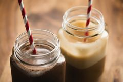 Warm cocoa and coffee in jar mugs on a wooden table Royalty Free Stock Images
