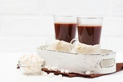 Warm cocoa in glasses with marshmallow, crocahet decorations, brown and beige napkins on white wooden background. Hot chocolate. S. Weet drink. Close up Stock Photo