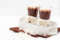 Warm cocoa in glasses with marshmallow, crocahet decorations, brown and beige napkins on white wooden background. Hot chocolate. S. Weet drink. Close up Royalty Free Stock Image