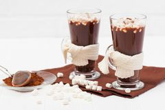 Warm cocoa in glasses with marshmallow, crocahet decorations, brown and beige napkins on white wooden background. Hot chocolate. S. Weet drink. Close up Stock Images