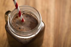 Warm cocoa in jar mug on a wooden table Stock Images