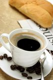 Warm coffee and bread. A cup of warm coffee and bread and paper on a morning table stock images