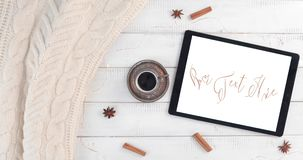Warm Coffee Break. Coffee cup, tablet computer and wool sweater on a white wooden table - Concept of freelance activity - Coffee break in a warm and cozy stock footage