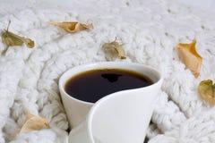 Warm coffee white mug. Coffee mug on white wool blanket, with autumn leaves a round Royalty Free Stock Photos