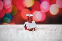Warm color Christmas photography image with cute little tree decoration of red house in snow with pink fairy lights in background Royalty Free Stock Photo