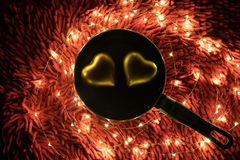 A warm color light garland surrounding two hearts inside pan. valentine`s day stock photos