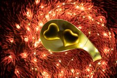 A warm color light garland surrounding two hearts inside plate. valentine`s day royalty free stock images