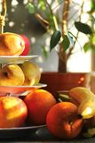 Warm color sunlit pears apples oranges and bananas fruits on three tier porcelain stand server next to a ficus pot plant. On window sill Royalty Free Stock Photo