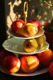 Warm color sunlit pears apples oranges fruits on three tier porcelain stand server next to a ficus pot plant on window sill. Against brown wall Stock Images