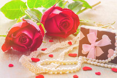 Warm color tone of couple of red rose with heart, pearl ornament and gift box decoration. Photo is focused at the left rose Stock Images