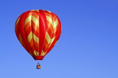 Warm Colored Hot Air Balloon. A warm-colored hot air balloon floats in a clear blue sky Royalty Free Stock Image