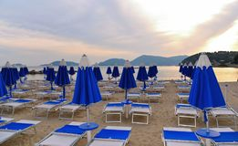 Warm colorful sunset on empty beach with blue chaise longues and calm sea water with old castle in background in Lerici, Liguria,. Italy, portovenere stock photo