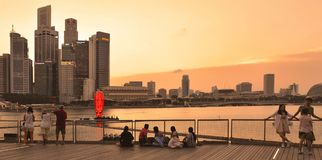 Warm colorful sunset on modern buildings and architectures in Marina Bay Sands with people relaxing on docks and watching skyline. On water in Singapore Royalty Free Stock Photo