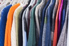 Colorful, cozy knitted sweaters hanging fro hangers. Warm, colorful sweaters hang on hangers at an outdoor market. Beautiful clothes for winter autumn season stock photography