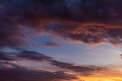 The warm colors contrast with the celestial one of the sky. Isolated clouds during sunset. The warm colors contrast with the celestial one of the sky stock images