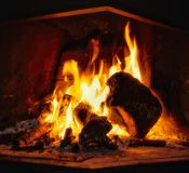 Warm and confortable fireplace. Great winter fireplace with burning logs and flames as a confortable ending day interior royalty free stock image