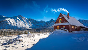 Warm cottage in winter mountain day Royalty Free Stock Photo