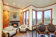 Warm cozy family room with of a luxury mansion house. Cream walls accented with brown trim paired with antique wood carved armchairs placed in front of stone Stock Image