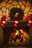 Warm cozy fireplace decorated for Christmas with real wood burni Stock Image