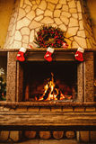 Warm cozy fireplace decorated for Christmas with real wood burni Royalty Free Stock Photos