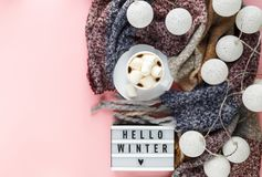 Warm, cozy winter clothing, scarf, lightbox and cup of coffee with white marshmallow stock photo