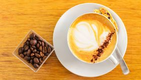Warm cup of cappucino with beam on brown background. Royalty Free Stock Photography