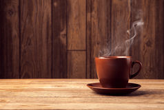 Warm cup of coffee on brown background Royalty Free Stock Photos