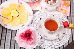 Warm cup of tea, heart shaped cake and sweets Royalty Free Stock Images